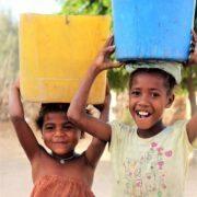 young girls carrying water